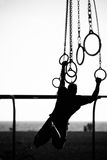 Silhouette of a person swinging on rings Royalty Free Stock Photos
