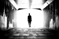 Silhouette of a person in the tunnel. Walking forward. Bright light shines in the background stock images