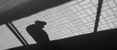 Silhouette person in an underground passage. Silhouette person bow-backed, hunched crooked man in underground passage. Shadow and light on paving slab. Inverted Stock Images