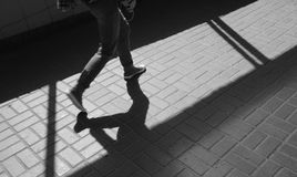 Silhouette person in an underground passage. Silhouette person, man walking in sneakers in underground passage. Shadow and light on paving slab. Exit from subway Stock Photos