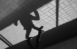 Silhouette person in an underground passage. Silhouette person, man in underground passage. People silhouette. Shadow and light on paving slab. Enter to metro Royalty Free Stock Images