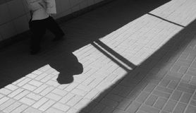 Silhouette person in an underground passage. Silhouette person, woman walking  in underground passage. Shadow and light on paving slab. Exit from subway Stock Images