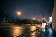 Silhouette of a person waiting in a city bus stop at night. In Chicago Stock Photos