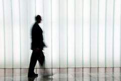 Silhouette of a person walking. Person walking in silhouette against a white patterned background Royalty Free Stock Images