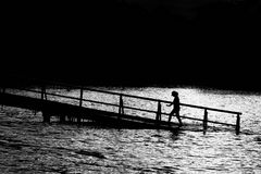 Silhouette of Person Walking on Black Bridge on Body of Water Stock Photos