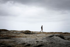 Silhouette of Person Walking on Grey Rock Mountain Stock Image