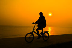 Silhouette of person who rides a bicycle near sea water with the s Royalty Free Stock Images