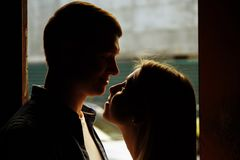 Silhouette photo. black faces.Close-up of kissing and embracing couples in old, doorway, family. date, attraction. Silhouette photo. black faces.Close-up of stock image
