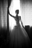Silhouette photo of bride holding shade at window Stock Images