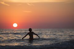 Silhouette Photo of Child on Body of Water during Golden Hour Royalty Free Stock Images