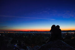 Silhouette Photo of Couple Sitting on Gray Boulder during Sunrise Royalty Free Stock Photo