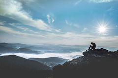 Silhouette Photo of Man Siting on Edge of Cliff during Daytime Stock Image