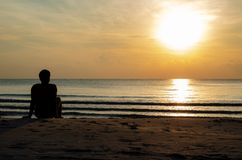The silhouette photo of a man sitting alone on the beach enjoy sunrise moment royalty free stock image
