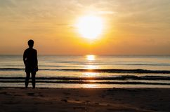 The silhouette photo of a man standing alone on the beach enjoy sunrise moment. With the reflection on the sea in summer season royalty free stock photo