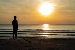 The silhouette photo of a man standing alone on the beach enjoy sunrise moment. With the reflection on the sea in summer season stock images
