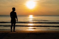 The silhouette photo of a man standing alone on the beach enjoy sunrise moment royalty free stock photo