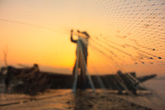 Silhouette photo. The old fisherman casting the net in the sunset. stock image