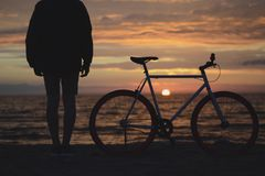 Silhouette Photo of a Person Beside a Mountain Bike Near the Sea at Sunset Royalty Free Stock Photos