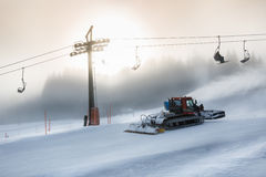 Silhouette photo of snow removal machine working on high ski slo Royalty Free Stock Image