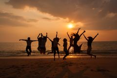 Silhouette photo of the team celebration on the beach at sunset stock photos