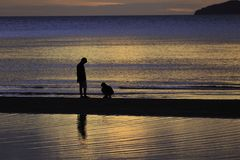 The silhouette photo of two brothers enjoy on the beach. With colorful sea in sunrise Royalty Free Stock Images