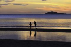 The silhouette photo of two brothers enjoy on the beach. With colorful sea in sunrise Stock Photos
