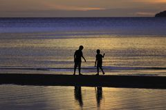 The silhouette photo of two brothers enjoy on the beach. With colorful sea in sunrise Royalty Free Stock Photography