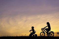 Two sisters riding bicycle. The silhouette photo of two sisters riding bicycle in the park with sweet sky at sunset stock image