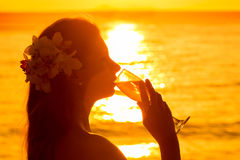 Silhouette photo of a woman drinking champagne from a glass at s Stock Photo