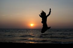 Silhouette photo of a woman jumping high on the beach. In Sri Lanka stock images