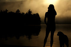 Silhouette Photo of a Woman Next to Dog Standing Beside Body of Water and Trees Stock Images