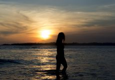 Silhouette photo of a woman standing in the ocean on the beach during sunset. In Sri Lanka stock photo