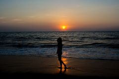 Silhouette photo of a woman walking on the beach during sunset. In Sri Lanka stock photography