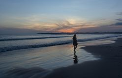 Silhouette photo of a woman walking on the beach during sunset. In Sri Lanka stock photo