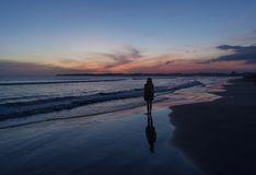 Silhouette photo of a woman walking on the beach during sunset time. In Sri Lanka royalty free stock image