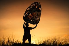 Silhouette man raise Thai shadow angel puppet. Silhouette photo of young man raising Thai shadow angel puppet at mountain meadow submit during sunset with copy Royalty Free Stock Photo