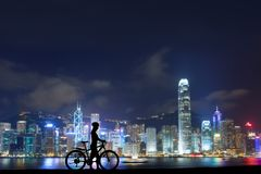 Silhouette photo of woman riding on bicycle. Silhouette photo of young woman riding on bicycle with modern night city in background stock photography