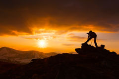 Silhouette of a photographer. Who shoots a sunset in the mountains Stock Photo