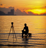 A silhouette of  photographer. Shooting for a sunrise Stock Photography