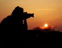 Silhouette of a photographer. A silhouette of photographer taking picture Royalty Free Stock Photo