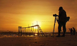 A silhouette of a photographer in action Royalty Free Stock Images