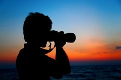Silhouette of photographer ashore on sunset Stock Photo