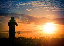 Silhouette photographer in grass field at sunset. Or sunshine background Royalty Free Stock Images