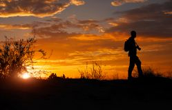 Silhouette of photographer with his camera at sunset stock photography