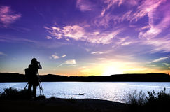 Silhouette of photographer with his equipment during sunset. Photographer in action on a beautiful sunset Stock Images