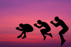 Silhouette photographer jumped in the sky. Stock Images