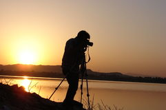 Silhouette of a Photographer at a lake at sunrise Royalty Free Stock Images