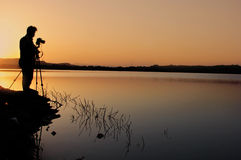 Silhouette of a Photographer at a lake at sunrise Stock Photography