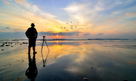 Silhouette of a photographer looking to the birds flying Royalty Free Stock Images