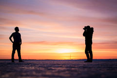 The silhouette of the photographer and man at. The silhouette of the photographer and men at sunset winter Stock Photos